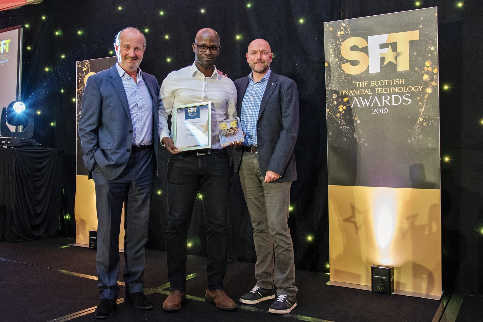 Gbenga Ibikunle collecting award at the Scottish Financial Technology Awards